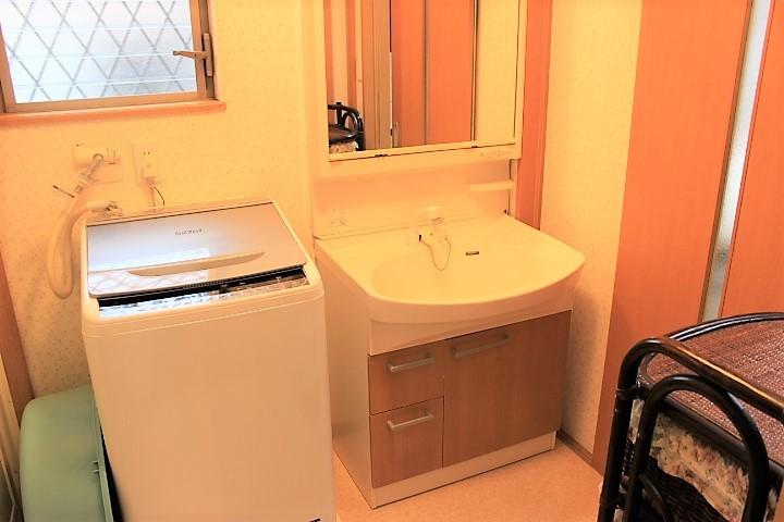 洗濯機を置いても広々とした洗面所 キッチンへ繋がり、便利な動線です