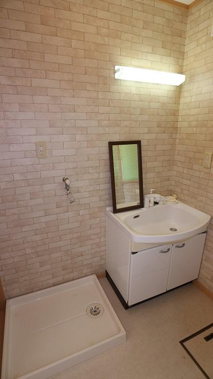 レンガ調の壁紙がおしゃれな洗面スペース。洗濯機を置くスペースもしっかり確保されています。