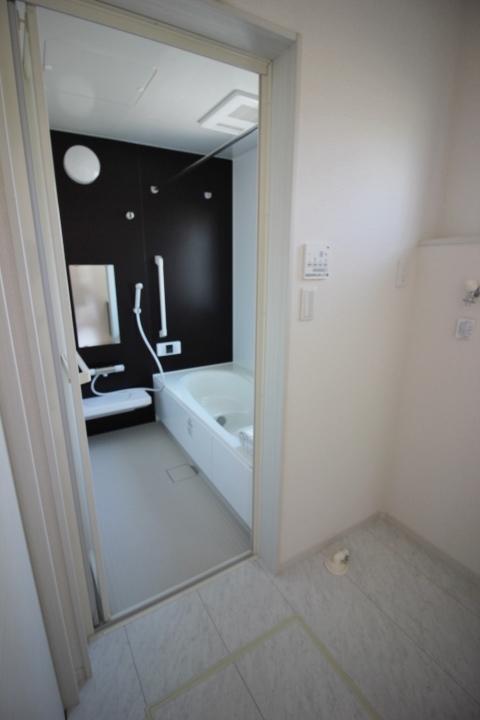 アクセント壁がシックなシステムバスルーム。半身浴もでき、節水効果もある浴槽でリラックスタイム。