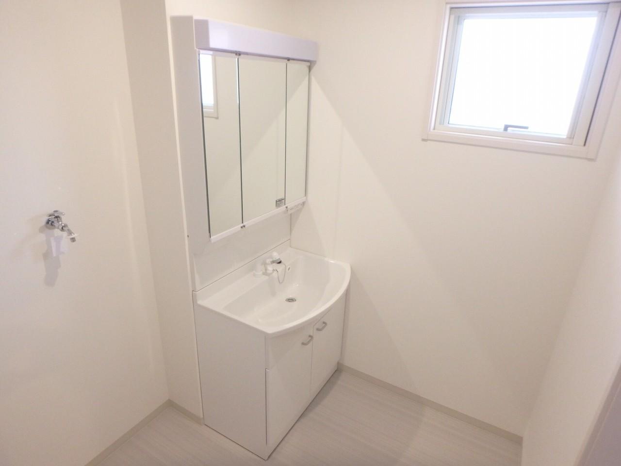 洗面台はシャワー水洗になっていますので洗濯や洗髪も出来ます。鏡は三面鏡になっており、コンセントがついているので朝の支度もしっかり出来ます。