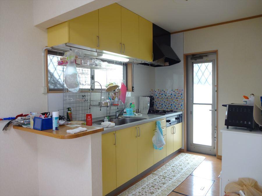 明るい黄色のキッチンボードが印象的な3口コンロのシステムキッチンです。