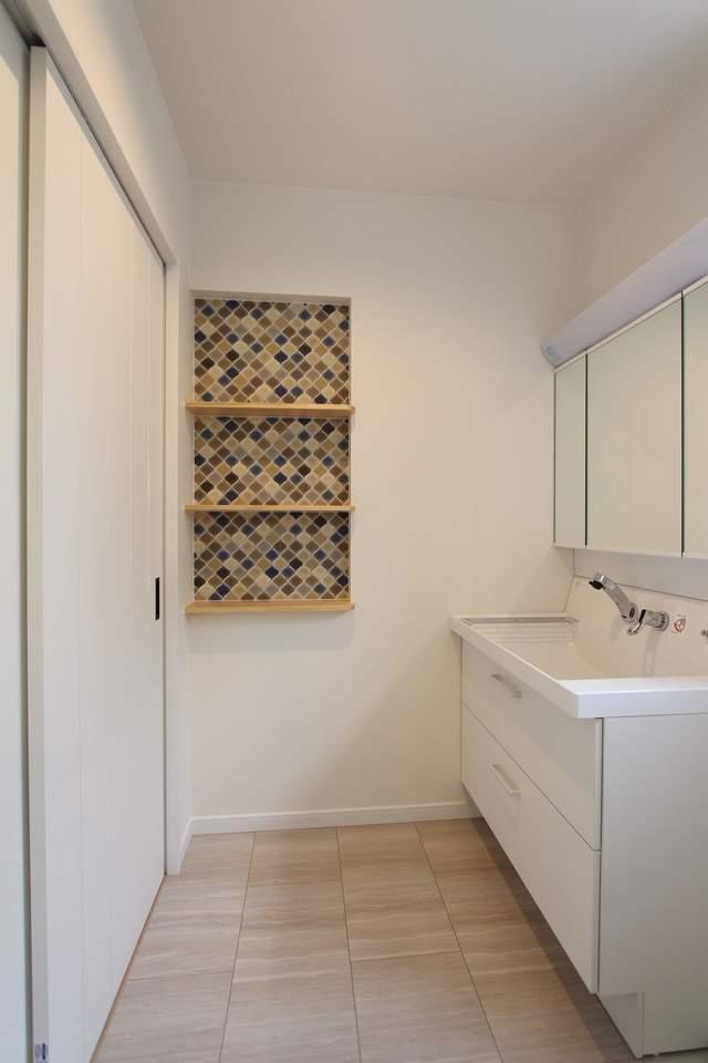 白を基調とした洗面所。洗面台の収納はたっぷり収納できて見渡しやすい引き出しタイプ。