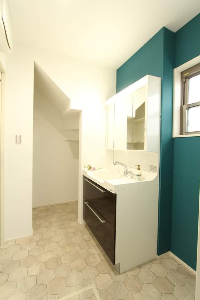 グリーンの壁紙がアクセントの洗面所。90cm幅の洗面台は、収納物を見渡せ取り出しやすい引き出しタイプの収納になっています。