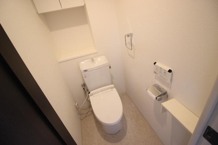 白を基調とした清潔感のあるトイレ 収納棚もあり使い勝手も良さそうです