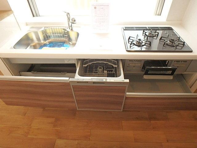 機能的なキッチン 食洗器や三口コンロが設置されています。
