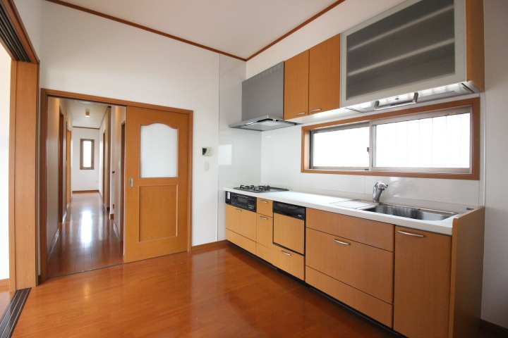 食器洗浄乾燥機がついたシステムキッチンは元気がでるカラー。窓付きなので手元が明るいキッチン