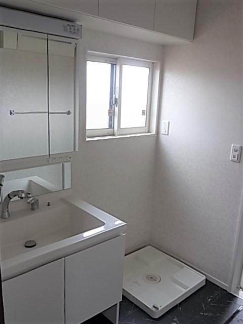 洗面台は白で、洗面所の床はお風呂の内装と合わせシックな色合いになってます