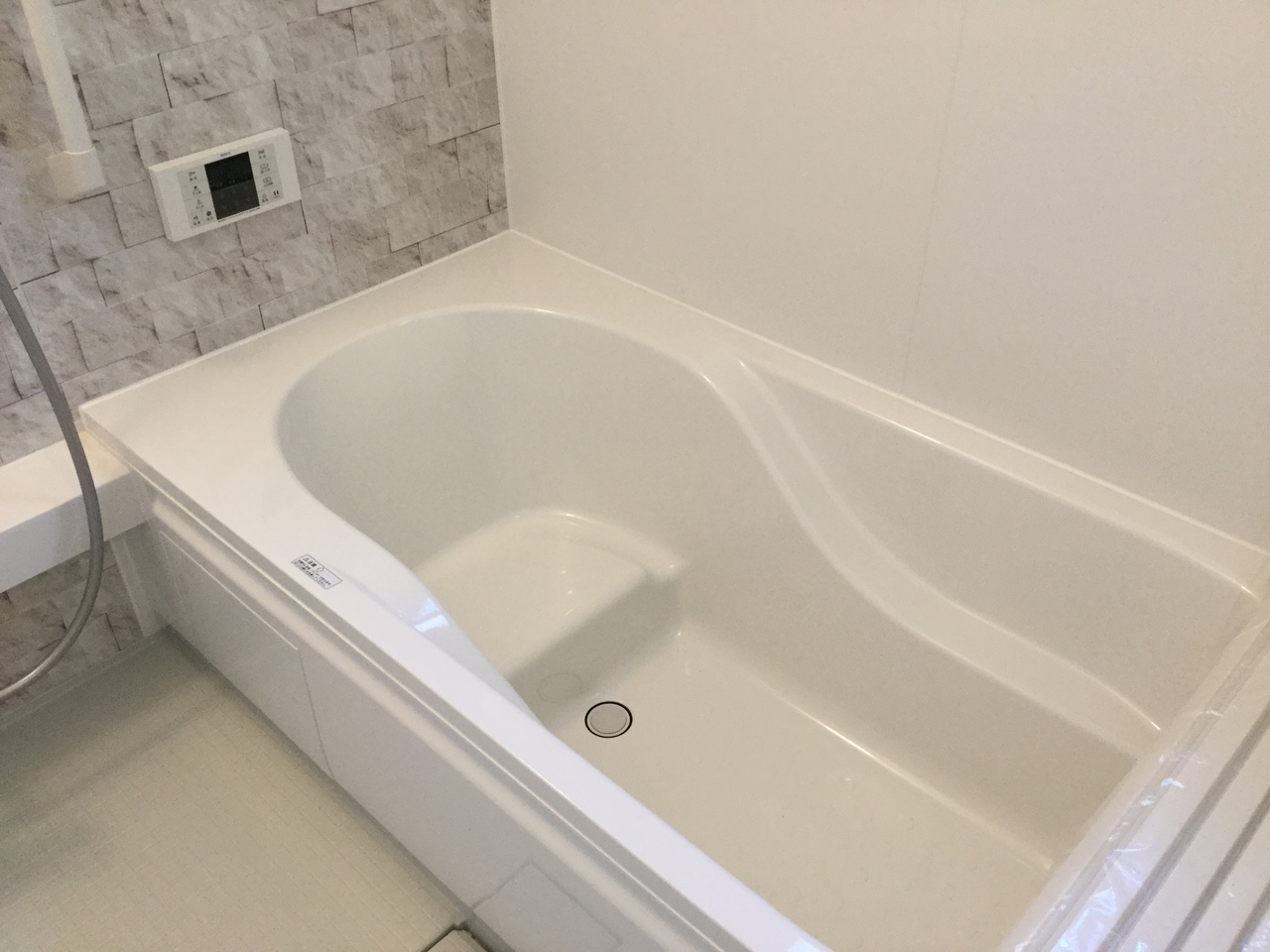 シックなトーンのシステムバスルーム。半身浴もでき、節水効果のある浴槽が採用されています。
