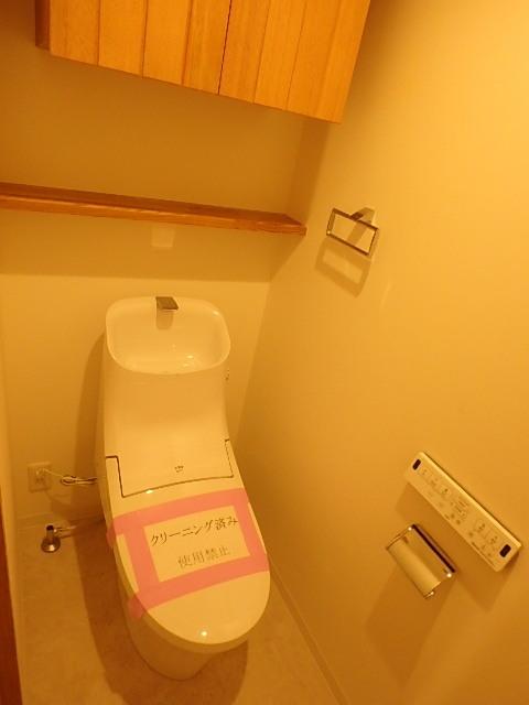 ウォシュレット機能付きのトイレ 上部に棚が設置されているので小物もしっかり収納できます。