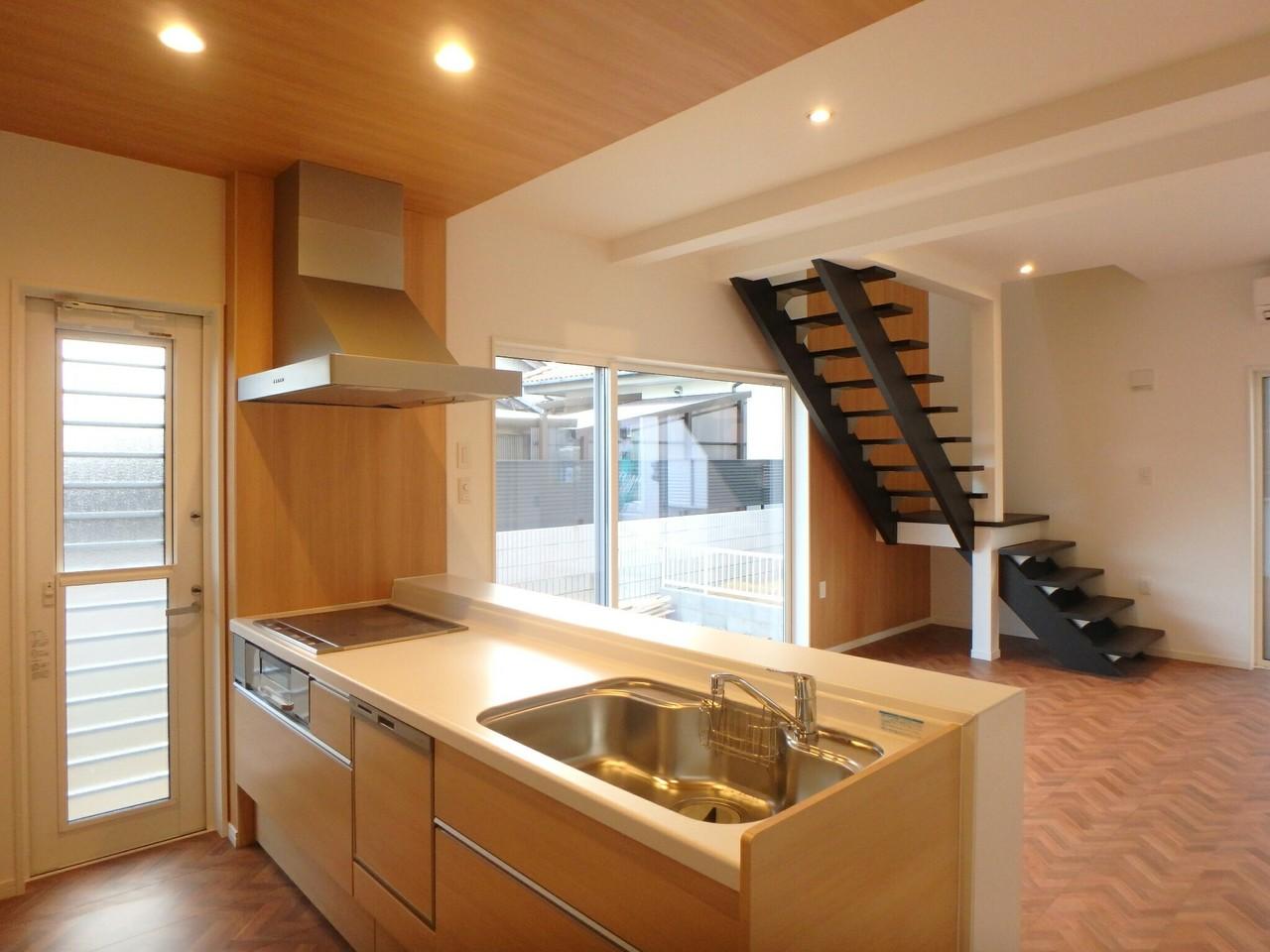 キッチンからはリビング、階段、庭が一望できます。 キッチンの色合いとリビングの床の色合いが統一されていて とってもおしゃれな空間となっています。