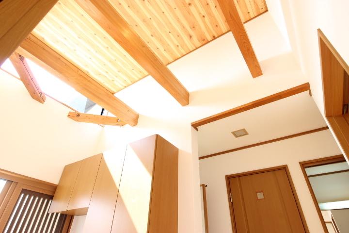 開放的な高い天井の小窓から自然な光が降り注ぐ玄関です