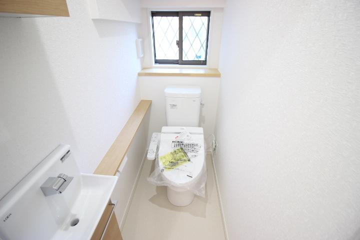 1階トイレ 手洗い場と棚が備えられているトイレは、清潔感のある洗浄便座