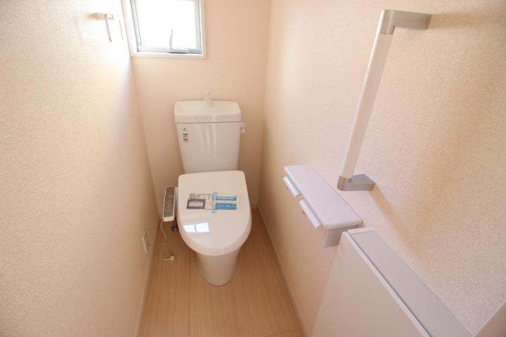 清潔感のある洗浄便座 手すりが備えられているのでお年よりも安心ですね