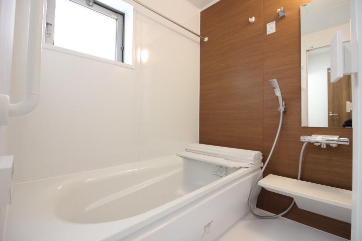 アクセント壁がシックなシステムバスルーム。半身浴もでき、節水効果もあるエコベンチ浴槽でリラックスタイム。
