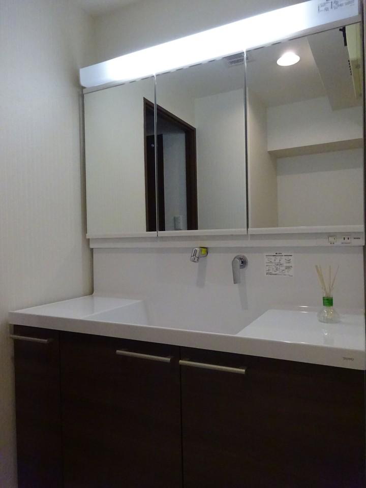 木目調の落ち着いた洗面台です。鏡も大きくて機能的です。