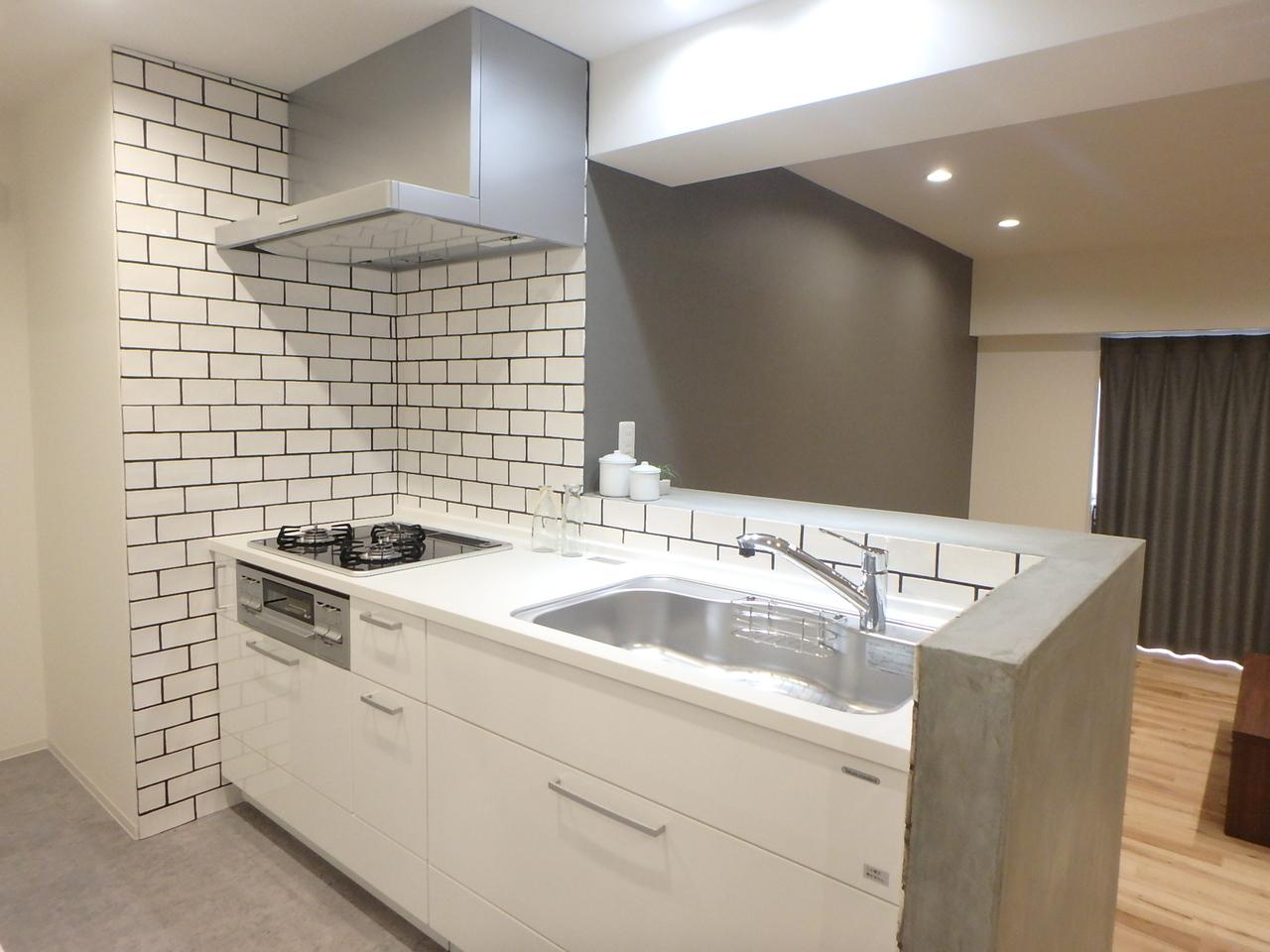 グレー&ホワイトで清潔感のあるキッチン。テレビを見ながら作業が可能。