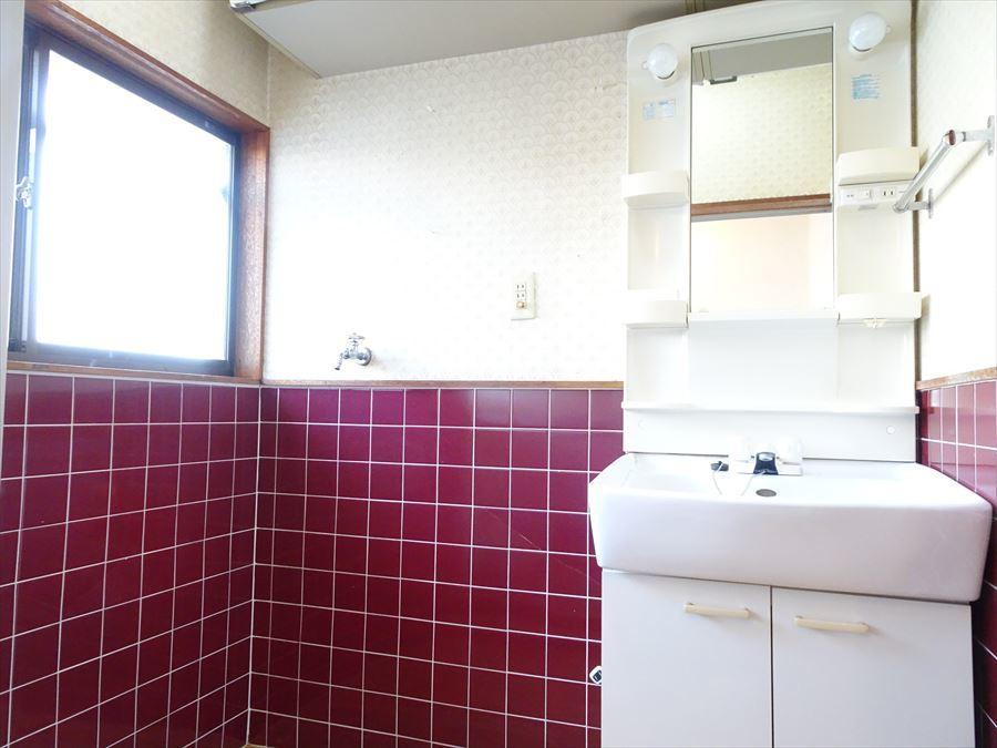 洗面室もタイルが貼られ、洗面台もきれいです。上には吊戸棚が設置されています。