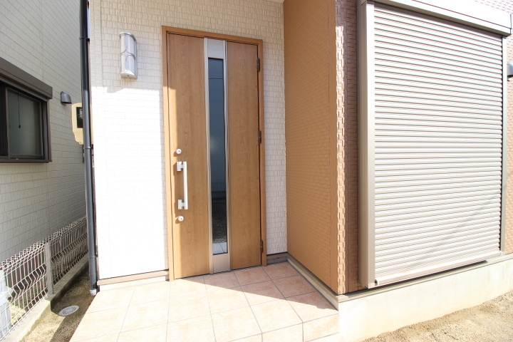 木目調の玄関ドアがポイントのエントランスは、屋根があるので雨の日の出入りも楽々