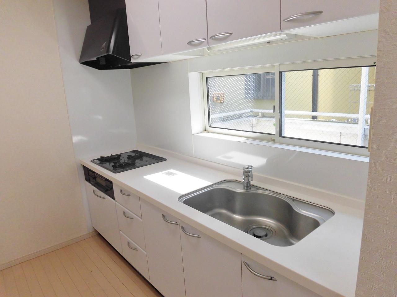 白を基調としたシステムキッチンです。人造大理石トップです。窓が有り明るいです。
